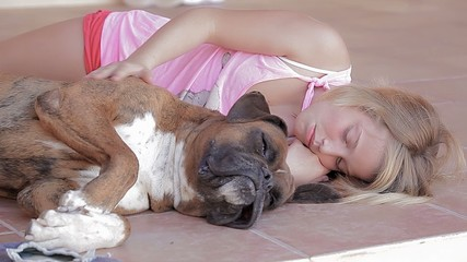 Little girl lying on side with her dog have fun