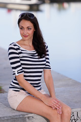 Attractive woman in stripes sitting on a ledge