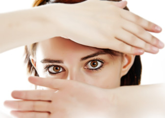 young face covered by hands