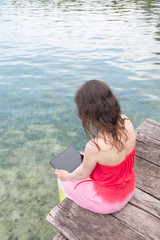 Woman working on the digital tablet at the edge of the pier
