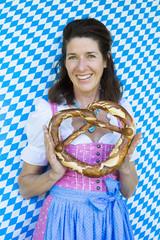 woman in dirndl with pretzel