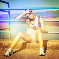 Tired jogger woman with smart phone sitting relaxing outdoors