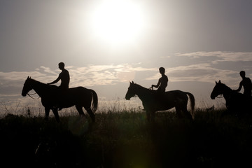People astride horses against a rising sun, it is tinted