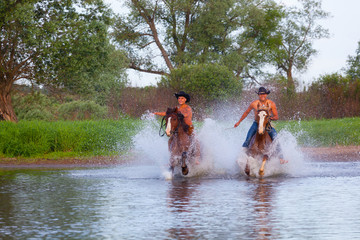 Young people skip astride horses through the river