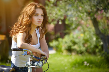 Pretty young woman with old bike in a country road.