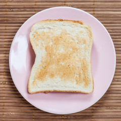 A golden brown slice of toast on a pink plate