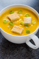Creamy pumpkin soup with croutons and finely chopped spring onio