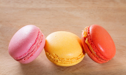French macarons on a wooden background.