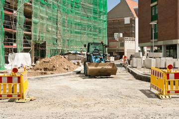 Strassenbauarbeiten vor einem eingerüstetem Neubau