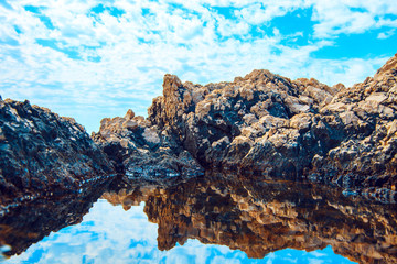 rocks and their reflection in the sea
