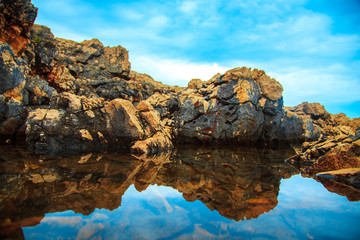 rocks and their reflection in the sea at daytime