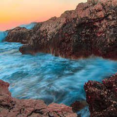 raging ocean waves breaking on rocks at sunset