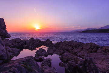 Horizontal photo of sunset on rocky beach