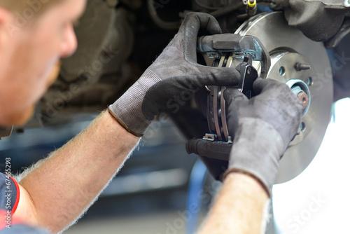 KFZ Mechaniker repariert Bremsen am Auto - 67465298