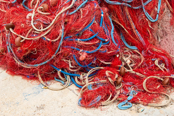 Heap of red fishing net and ropes on the quay.