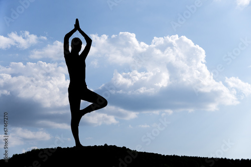 Poster Pretty woman doing yoga exercises in the park. silhouette.
