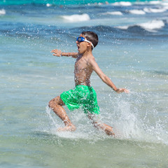 little boy running through the water on the beach
