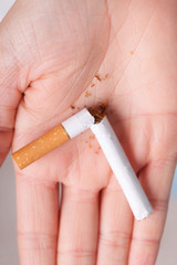 Addiction. Broken cigarette on hand. Quit smoking