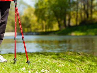 Nordic walking. Red sticks on grass in park