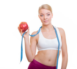 Diet. Fit girl with measure tape and apple fruit