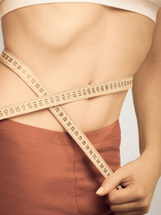 Weight loss, measuring tape on woman waistline