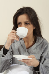 Worried - sick young woman sitting in bed with a hot drink.