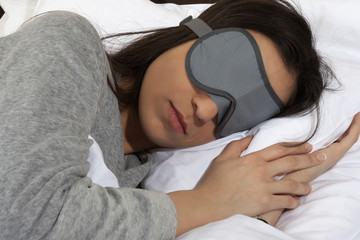 Young woman taking a nap during the day with sleeping mask.