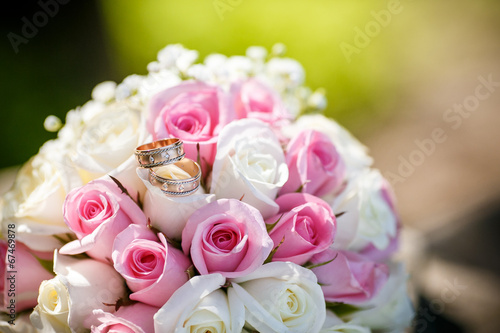 canvas print picture Wedding rings on a roses flowers, focused to the rings