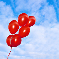 Red inflatable balloons on the sky background