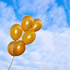 Golden flying balloons on the sky background