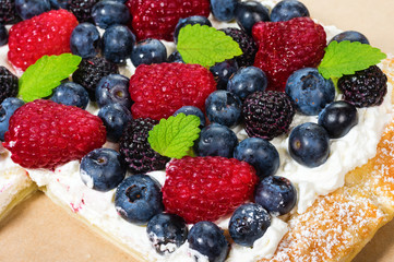 Fresh berry tart with cream overhead
