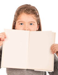 Little girl peeking from behind an open book