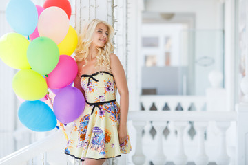 A young woman with large colourful latex balloons