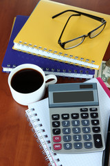 Office supplies with money and cup of coffee