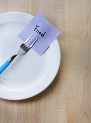 Note paper with message  attached to fork,