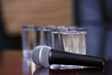 Microphone with glasses of water on table close-up
