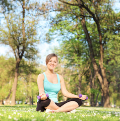 Young girl exercising with dumbbells in park