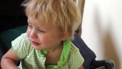 Crying two year old child in a buggy
