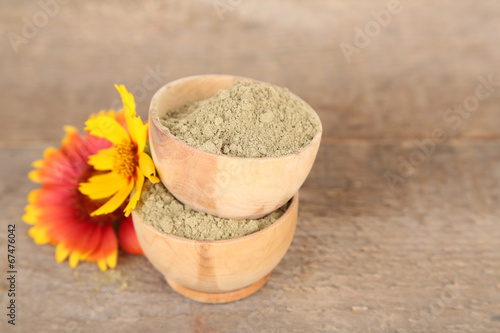 Dry henna powder in bowls on wooden table