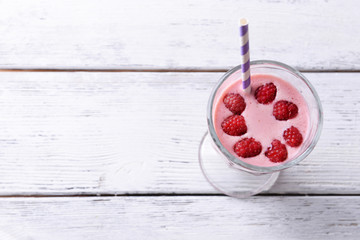 Glass of raspberry smoothie drink on wooden background