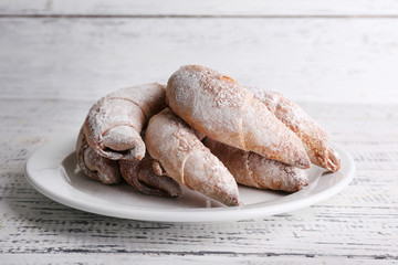 Tasty bagels with powdered sugar, on wooden background