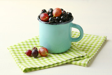 Ripe blackcurrants in mug on light wooden background.