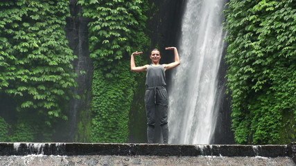 Happy woman enjoying amazing waterfall in Bali