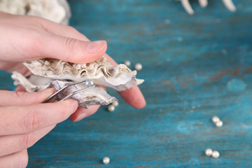 Hand with tweezers holding pearl and oyster on wooden