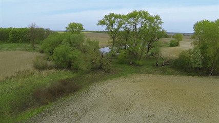 Flight  up over Field with river  and trees .Aerial