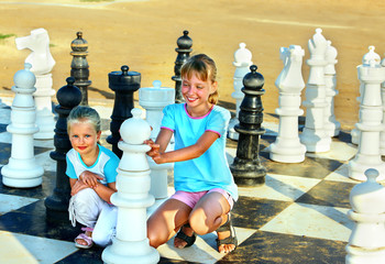 Children play chess outdoor.