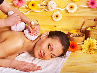 Woman getting herbal ball massage.
