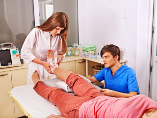 Doctor bandaging patient in hospital.