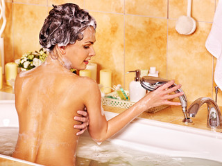 Woman using bath sponge in bathtub.