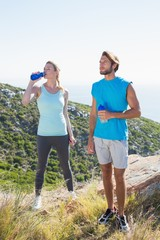 Fit couple standing drinking from water bottles
